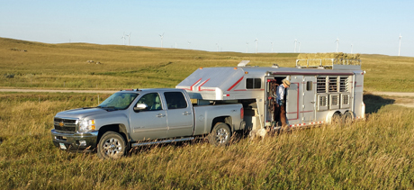 Truck and horse trailer are parked just off a gravel road. A section of the Tatanka Wind Farm is visible on the high Coteau des Prairie.