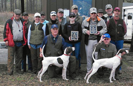 Tim Moore, on left, poses third place Elhew G Force while Sedge Surfer, winner of the stake, is on right. Standing behind Surfer and holding the plaque is his owner, Field Trial Hall-of-Famer Bill Perry. Jim Tande is the tall guy wearing a tan hat in the center of the back row.