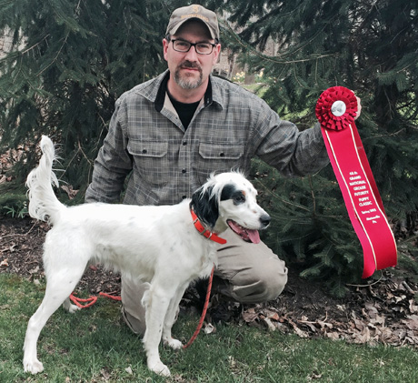 Tom Beauchamp proudly displays the big red ribbon won by Northwoods Iron Maiden (Northwoods Grits x CH I'm Blue Gert, 2014) for her second place finish in the Grand National Grouse Futurity Puppy Classic.