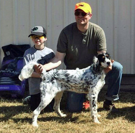 Matt Forgit and his son happily pose with Miles (CH Shadow Oak Bo x Northwoods Chardonnay, 2014) after his third place finish in the Open Puppy at a Minnesota Grouse Dog Association spring trial.