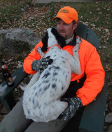 A typical scene after a day in the grouse woods at New Wood, a hunting camp in northern Wisconsin:  Chris Bye and his setter Piper.